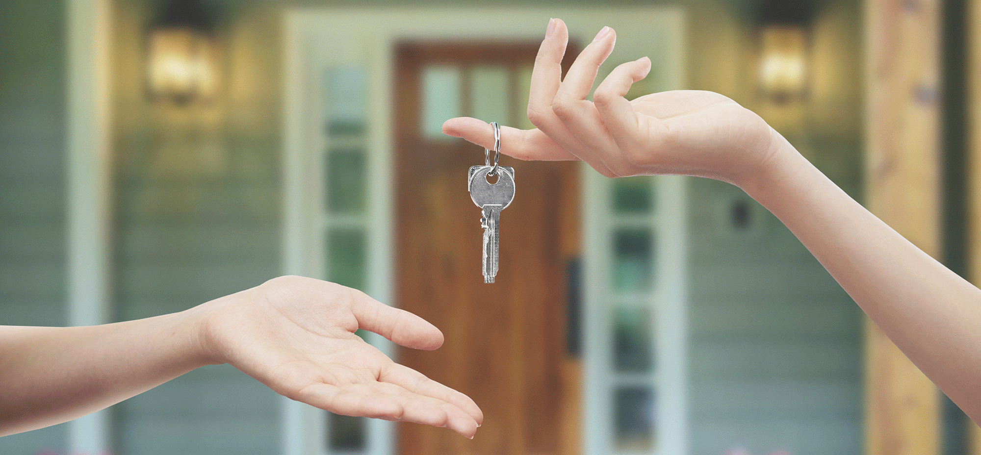 Two hands exchanging keys to a new home.